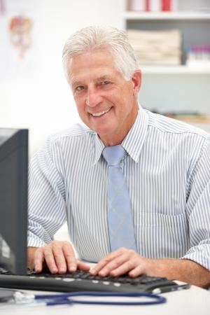 1 senior: M�dico jefe en el escritorio Foto de archivo