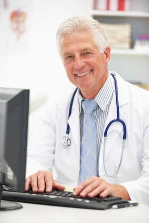 doctor computer: Senior doctor at desk Stock Photo