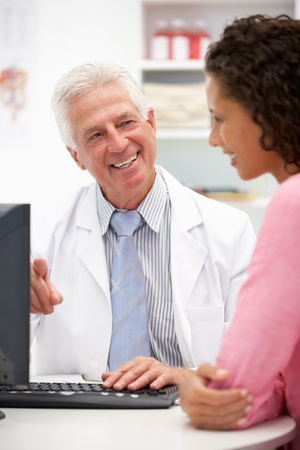 doctor computer: Senior doctor with female patient
