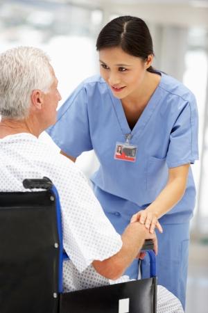 persona en silla de ruedas: Paciente mayor con el médico de los jóvenes Foto de archivo