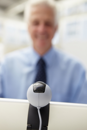 skype: Senior businessman using skype Stock Photo