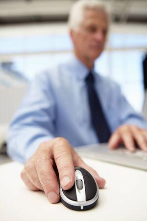 pressured: Senior businessman using laptop