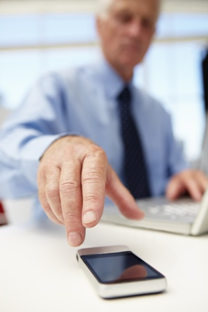 pressured: Senior businessman with laptop and phone