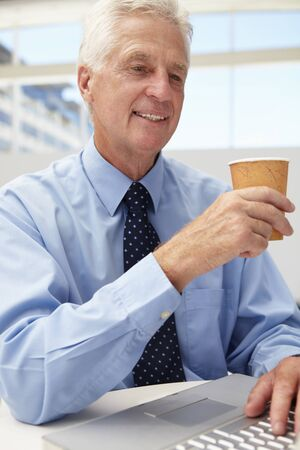 Senior businessman with laptop and coffee photo