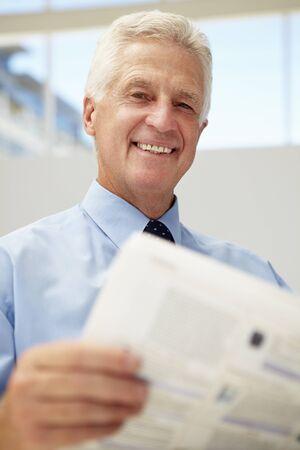 man holding book: Senior businessman reading document