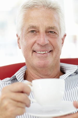Senior man relaxing with cup of tea photo