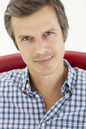 greying: Man sitting in red chair Stock Photo
