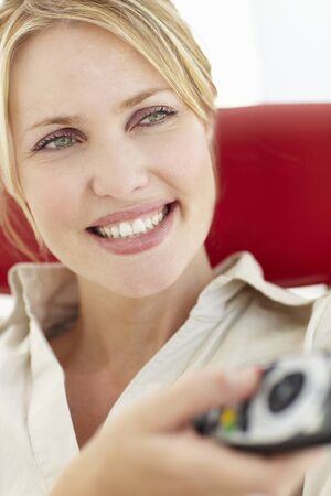 changing channel: Woman with remote control Stock Photo