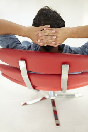 designer chair: Young man relaxing in red chair