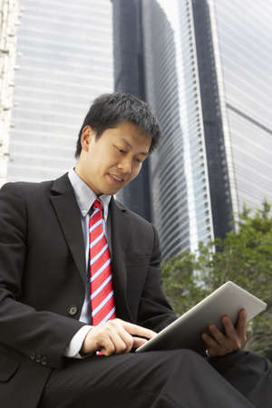 Chinese Businessman Working On Tablet Computer Outside Office Stock Photo - 18709471