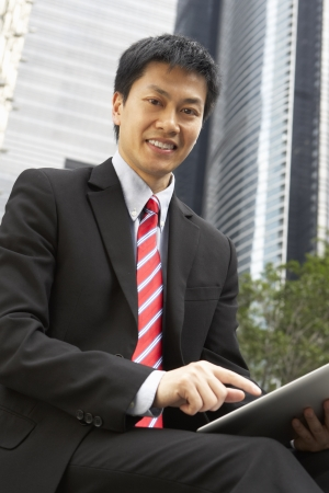 Chinese Businessman Working On Tablet Computer Outside Office Stock Photo - 18709479