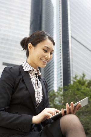 Chinese Businesswoman Working On Tablet Computer Outside Office Stock Photo - 18709640