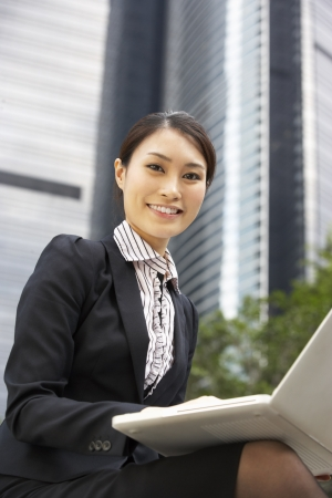 Chinese Businesswoman Working On Laptop Outside Office Stock Photo - 18709628