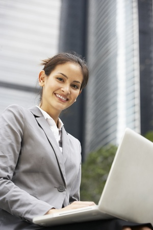 Hispanic Businesswoman Working On Laptop Outside Office Stock Photo - 18709759