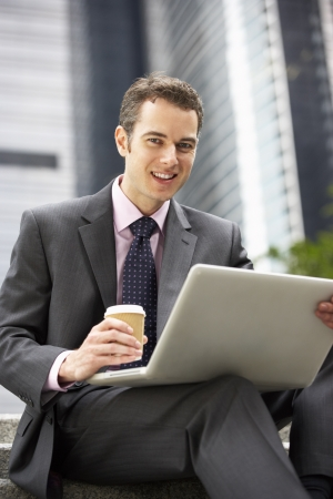 Businessman Working On Laptop Outside Office With Takeaway Coffee photo