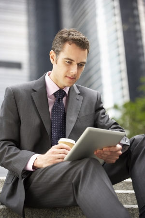 working attire: Businessman Working On Tablet Computer Outside Office With Takeaway Coffee