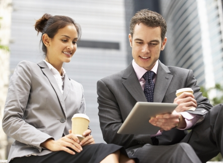 Businessman And Businesswoman Using Digital Tablet Outside Office photo