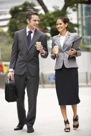 two people talking: Businessman And Businesswoman Walking Along Street Holding Takeaway Coffee Stock Photo