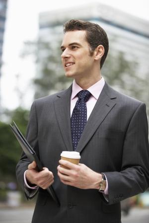 Businessman Walking Along Street Holding Takeaway Coffee photo