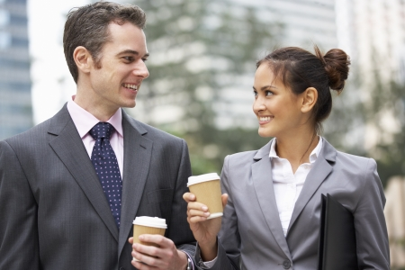 Businessman And Businesswoman Chatting In Street Holding Takeaway Coffee photo
