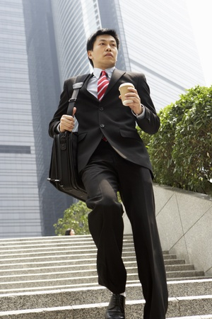 haste: Chinese Businessman Rushing Down Steps Carrying Bag And Takeaway Coffee Stock Photo