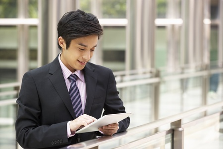 Chinese Businessman Working On Tablet Computer Outside Office Stock Photo - 18709646