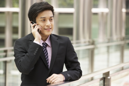 chinese business: Chinese Businessman Outside Office On Mobile Phone