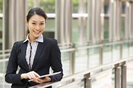 Chinese Businesswoman Working On Tablet Computer Outside Office Stock Photo - 18709452