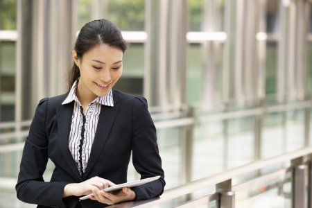 Chinese Businesswoman Working On Tablet Computer Outside Office Stock Photo - 18709624