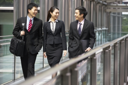 asian office lady: Three Business Colleagues Having Discussion Whilst Walking Outside Office