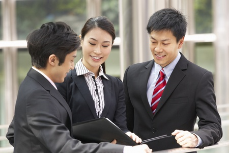 business scene: Three Business Colleagues Discussing Document Outside Office Stock Photo