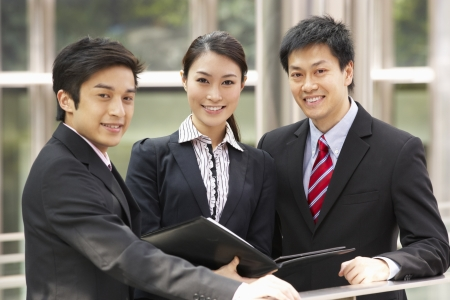kong: Portrait Of Three Business Colleagues Discussing Document Outside Office