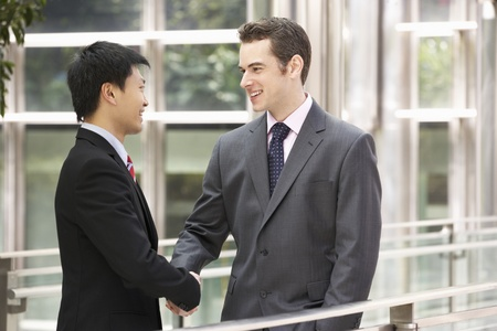 dos personas hablando: Dos hombres de negocios Estrechar las manos fuera de la oficina Foto de archivo