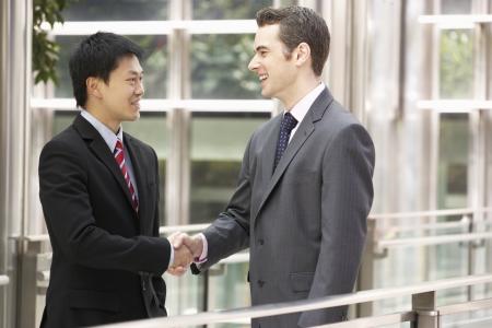 deux personnes qui parlent: Deux hommes d'affaires se serrant la main devant le bureau de