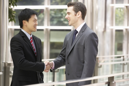 Two Businessmen Shaking Hands Outside Office photo