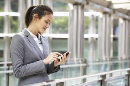 texting: Hispanic Businesswoman Outside Office On Mobile Phone