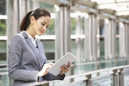 gente sentada: Empresaria hisp�nica que trabaja en la computadora de la tableta fuera de la oficina