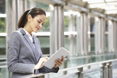 business scene: Hispanic Businesswoman Working On Tablet Computer Outside Office