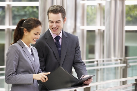 two people talking: Businessman And Businesswoman Discussing Document Outside Office