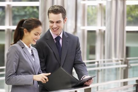 dos personas conversando: Hombre de negocios y empresaria examinar el documento fuera de la oficina