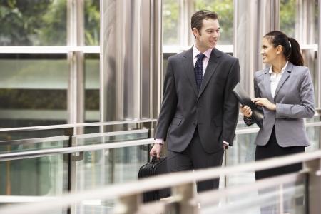 personas caminando: Dos colegas de negocios tener discusi�n mientras caminaba Oficina Exterior