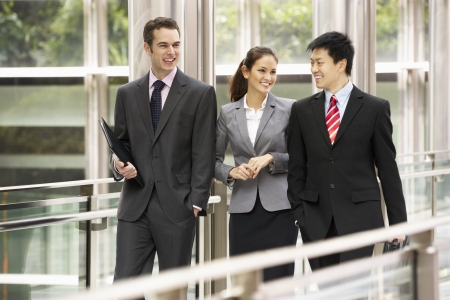 business people walking: Three Business Colleagues Having Discussion Whilst Walking Outside Office