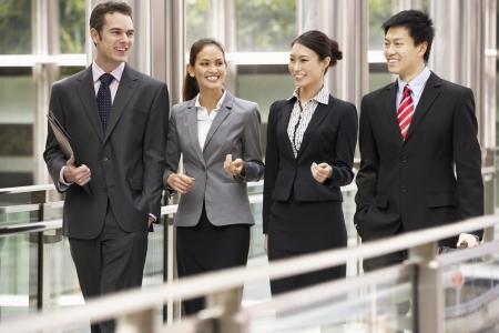 четыре человека: Четыре коллег по бизнесу с обсуждения во время ходьбы у офиса Фото со стока