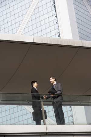 Two Businessmen Shaking Hands Outside Office Building photo
