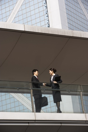 welcoming: Two Business Colleagues Shaking Hands Outside Office Building