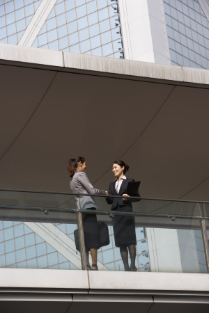 Two Businesswomen Shaking Hands Outside Office Building photo