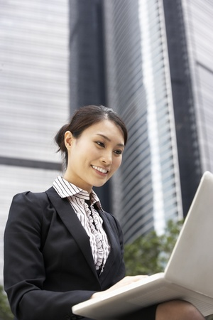 Chinese Businesswoman Working On Laptop Outside Office Stock Photo - 18709648