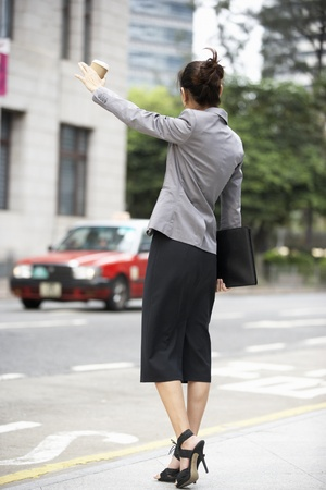 Businesswoman Hailing Taxi In Busy Street photo