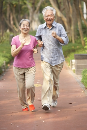 Senior Chinese Couple Jogging In Park Stock Photo - 18710534