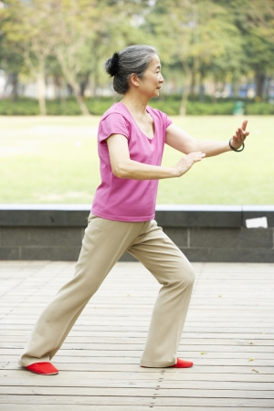 Senior Chinese Woman Doing Tai Chi In Park photo